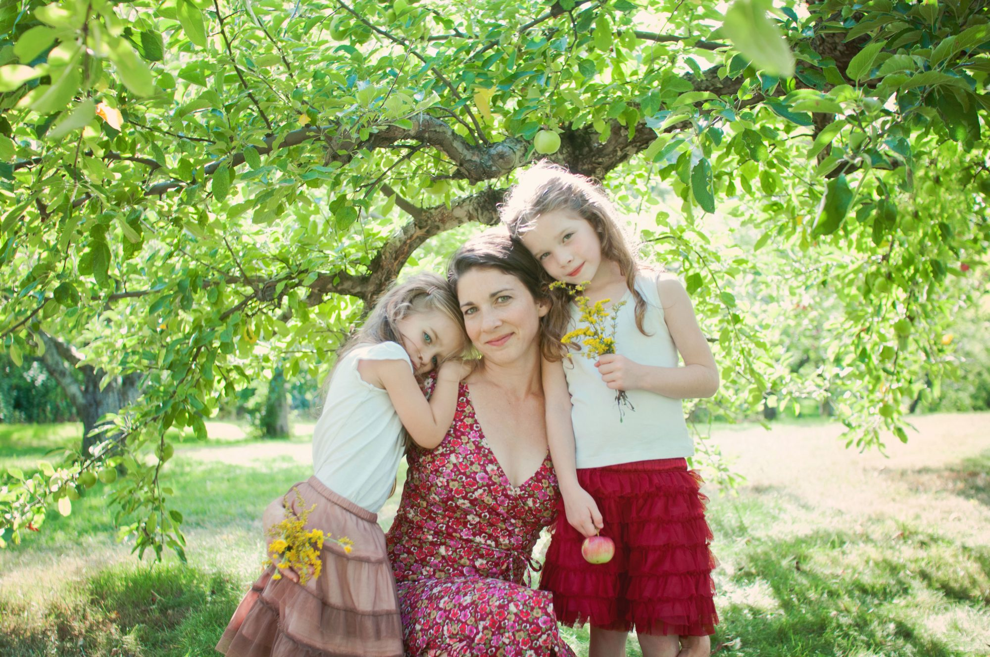Portrait of mother and two daughters beneath an apple tree