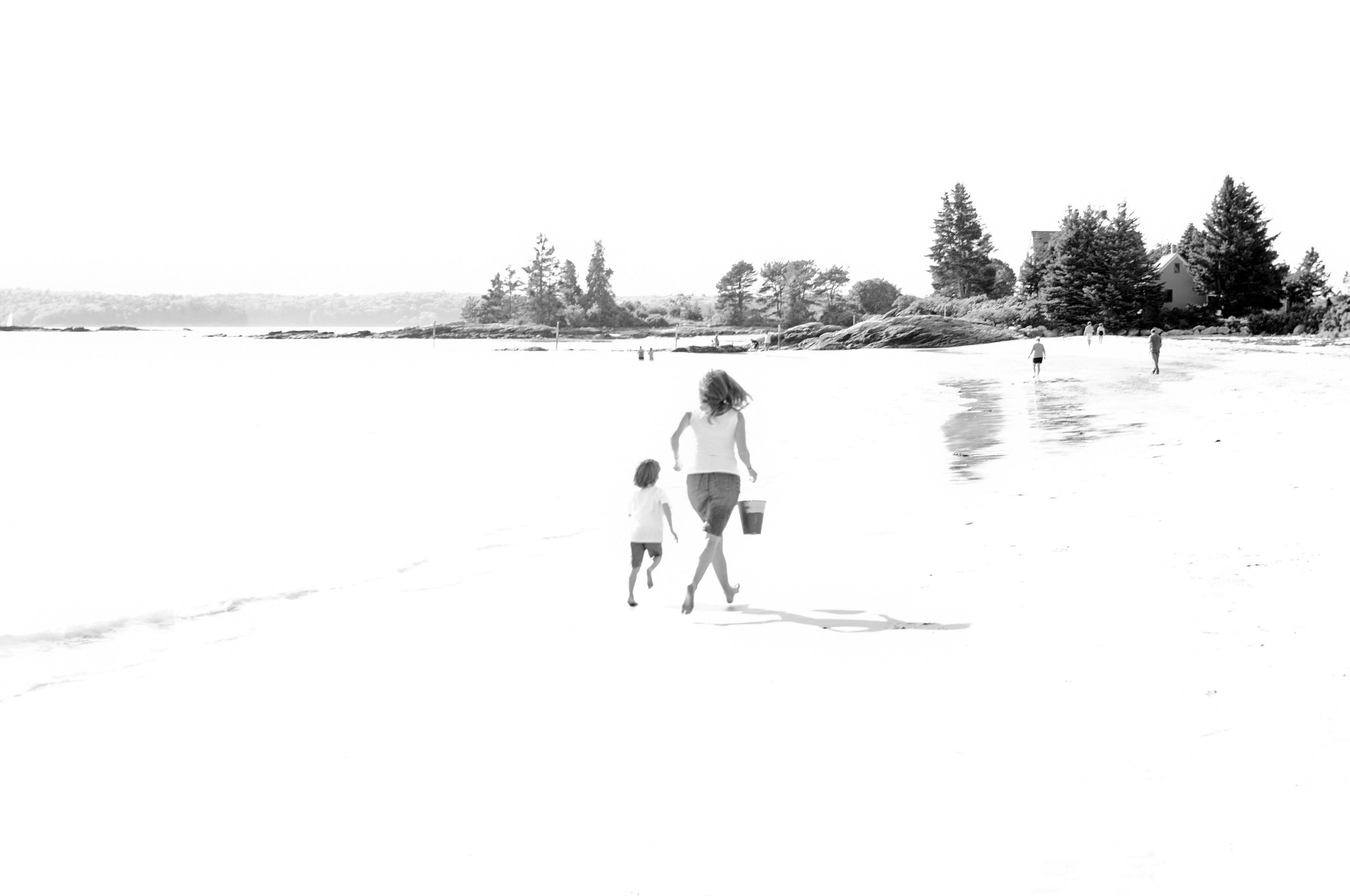 Over blown black and white of mother and child running at Pemaquid Beach