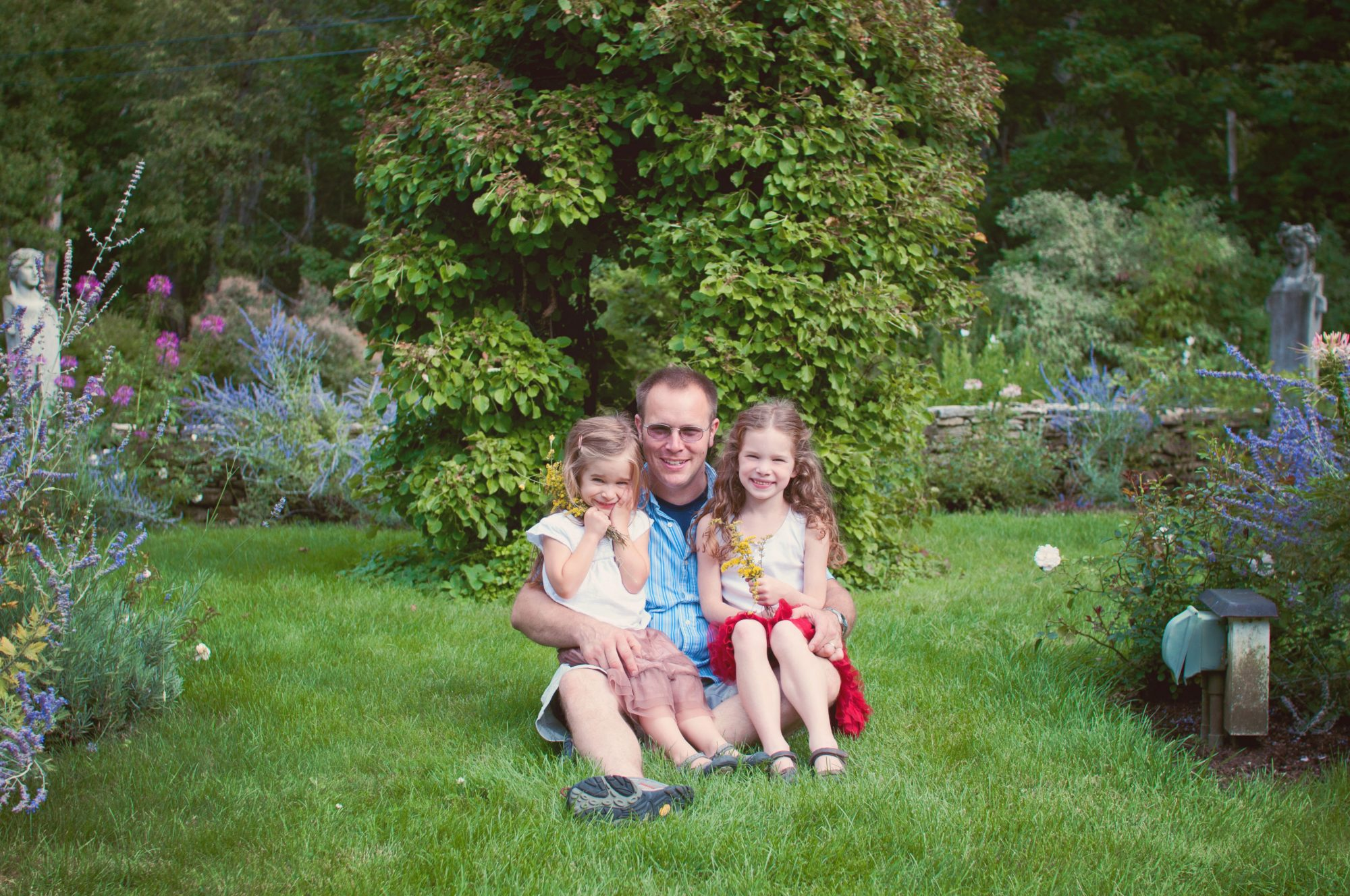 Father and two daughters in a garden