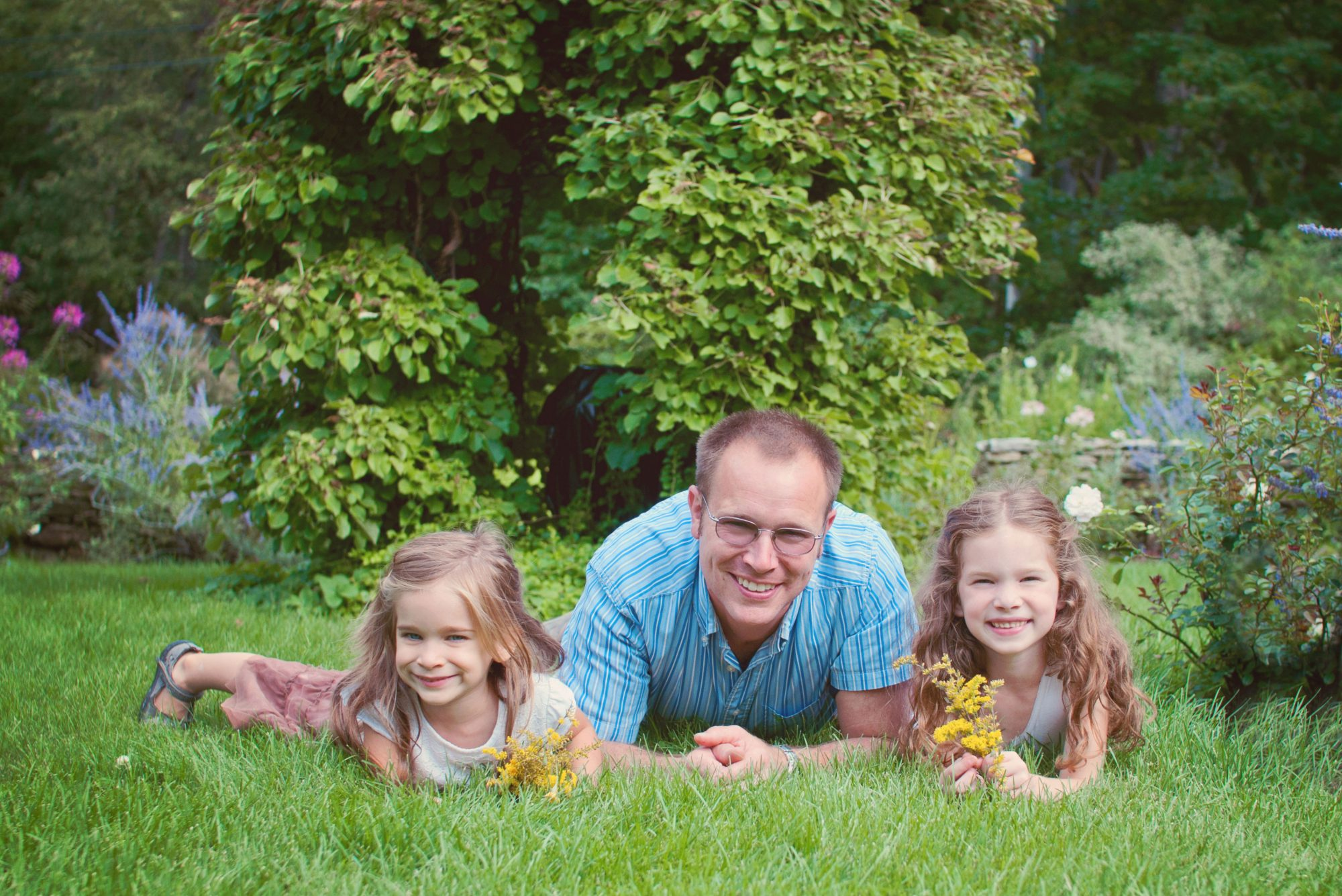 Father and daughters in garden at Clark's Cove Farm