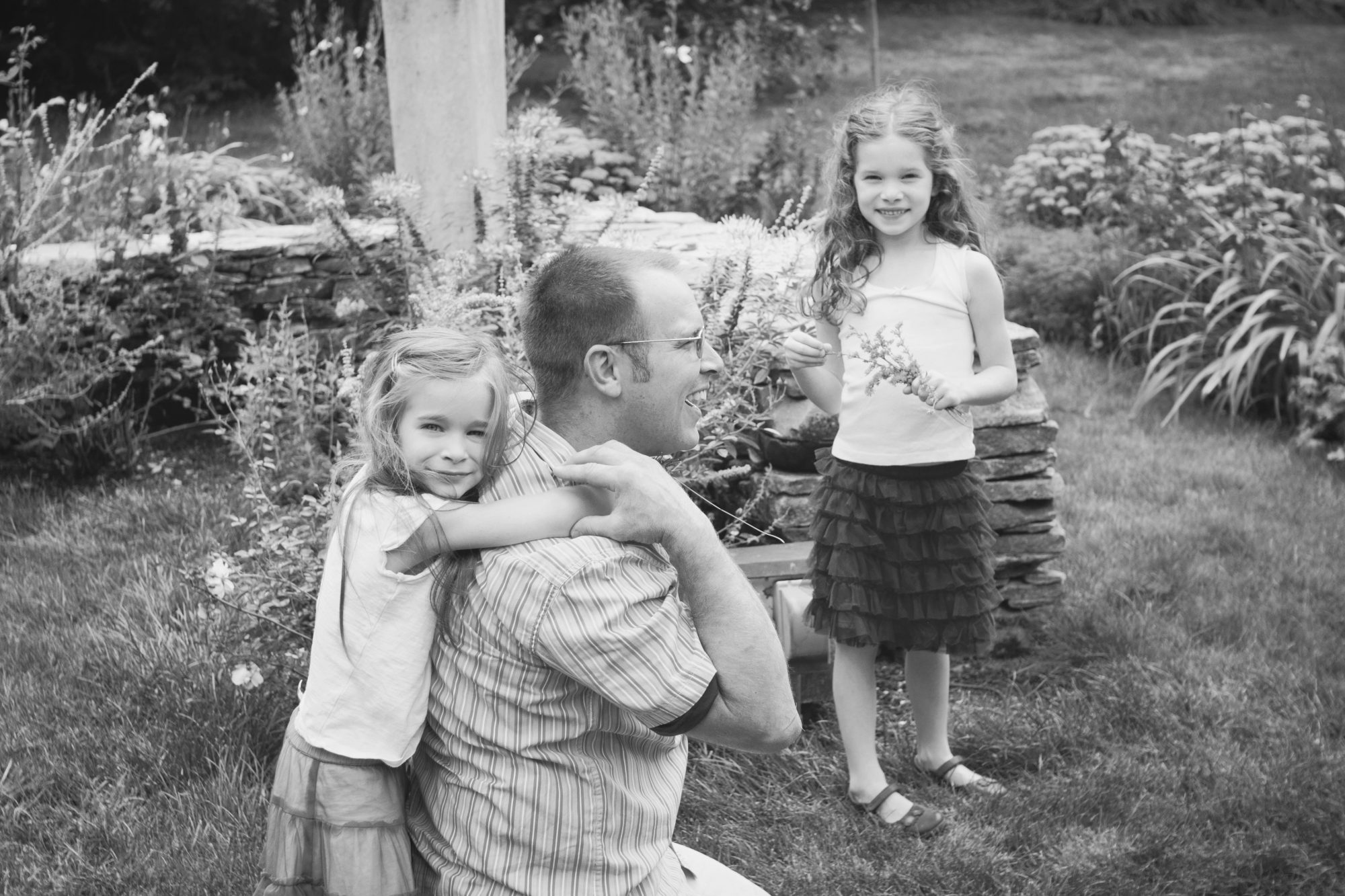 Black and white photo of father with two daughters