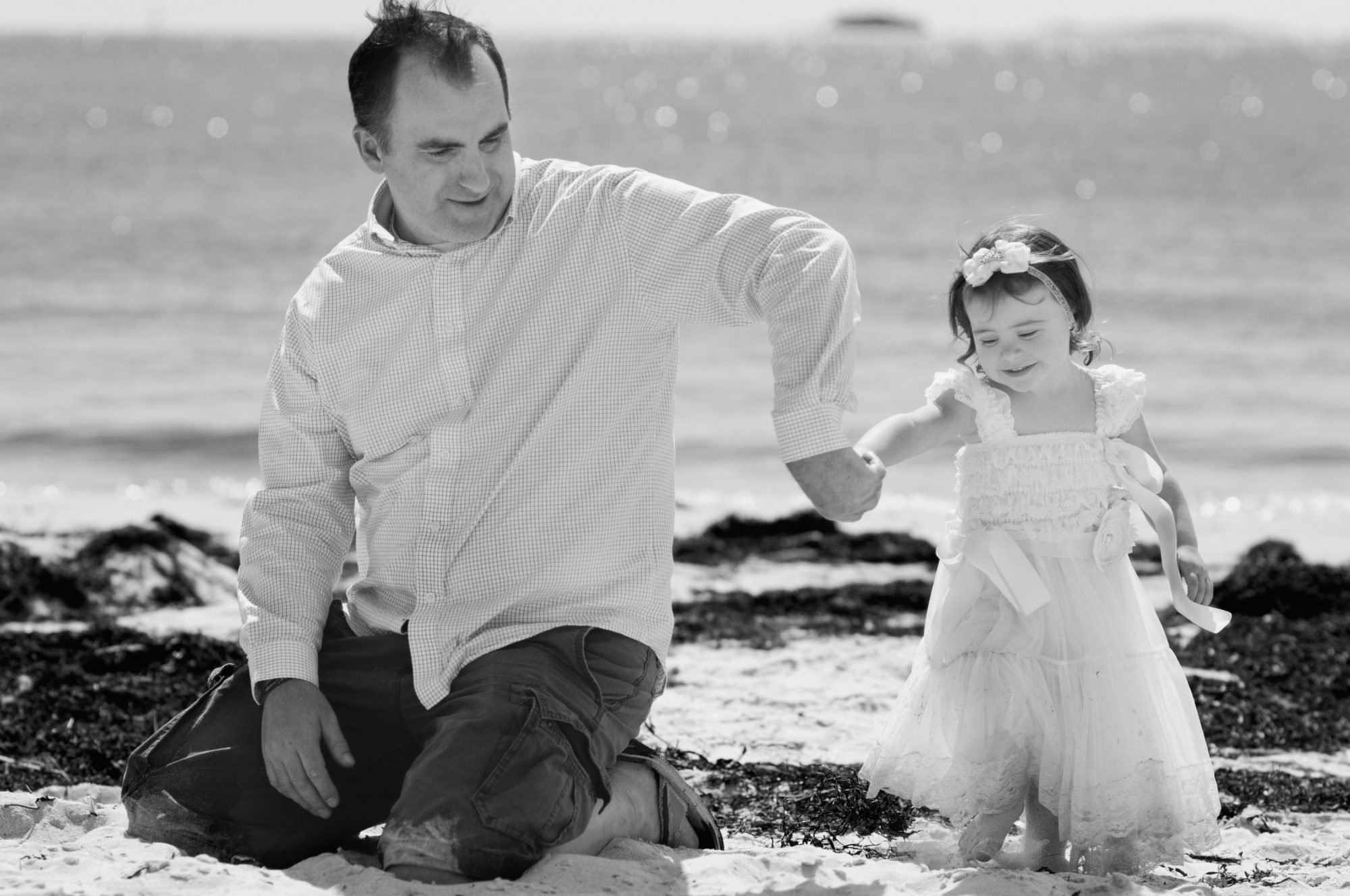 Father and daughter playing in the sand at Pemaquid Beach, Maine.