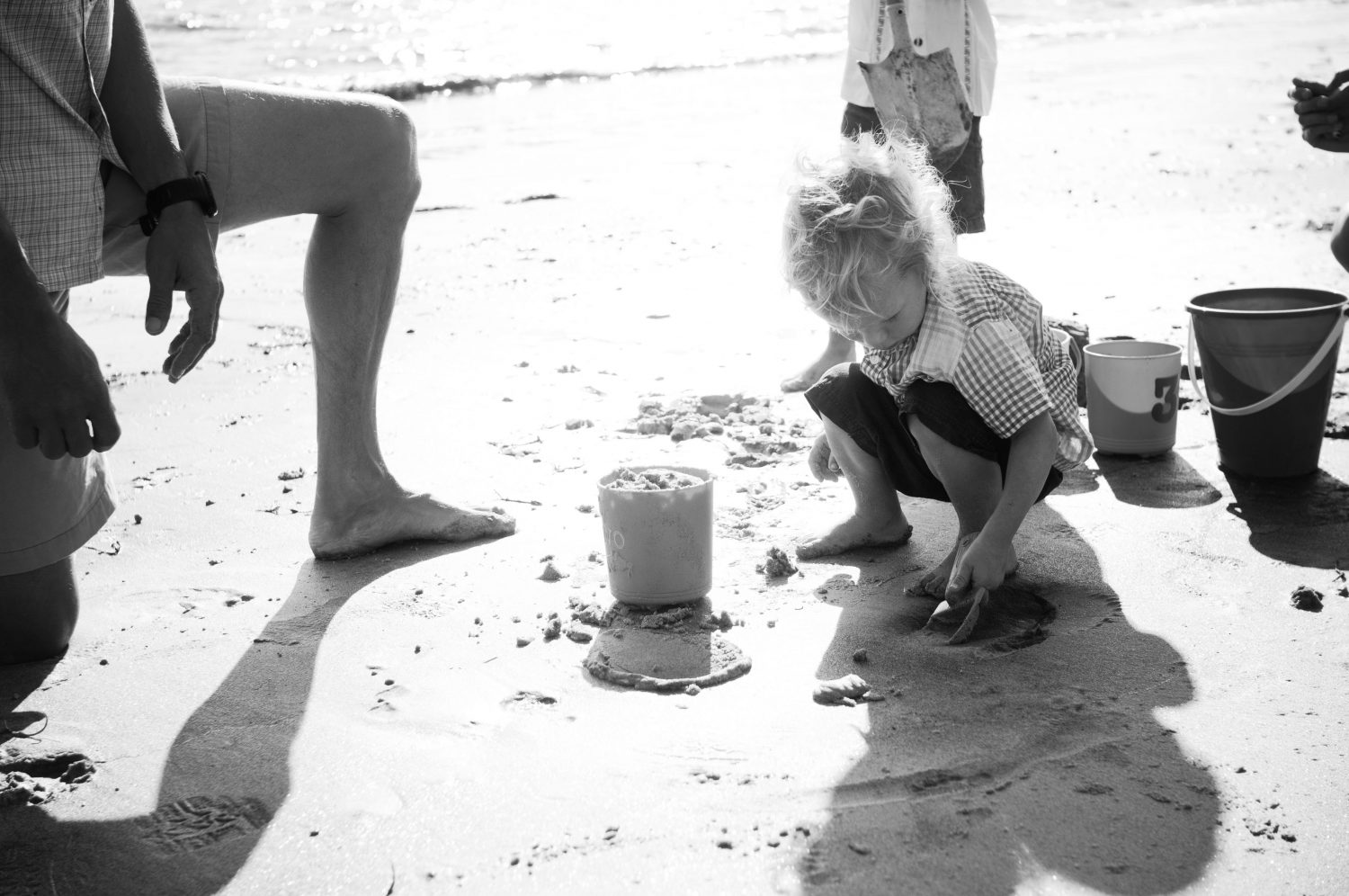 Toddler playing with sand bucket at Pemaquid Beach