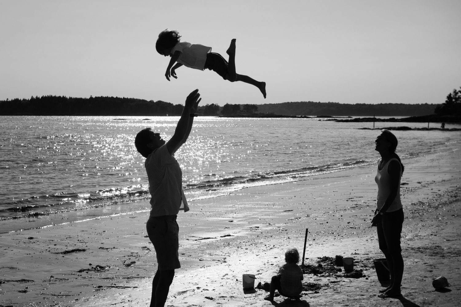 Black and white photo of father tossing son into the air as a game at Pemaquid Beach