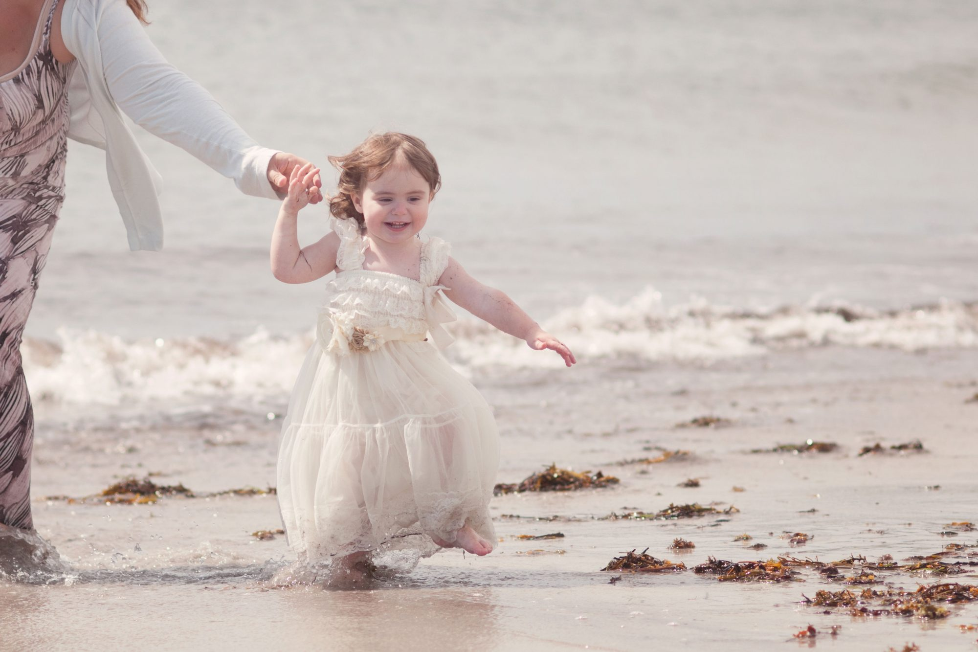 Little girl giggeling at the beach with mom