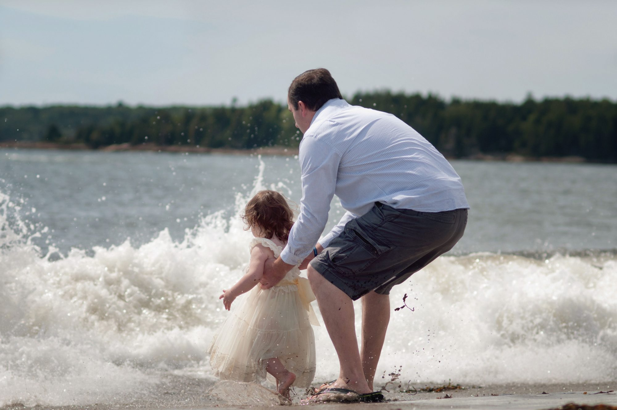Dad making sure his daughter doesn't get too close to the crashing waves.