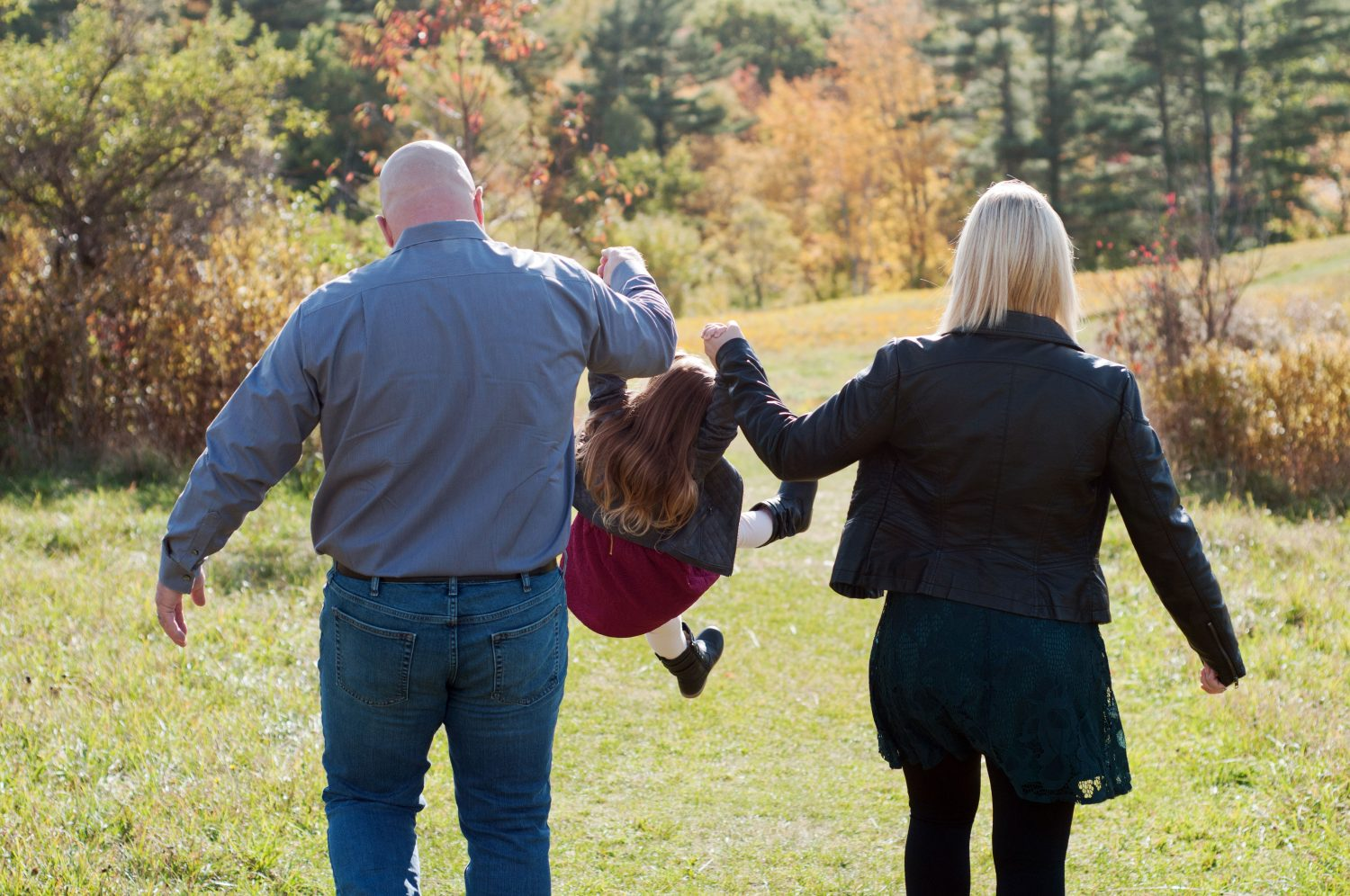 young family of three walking in a field in the fall