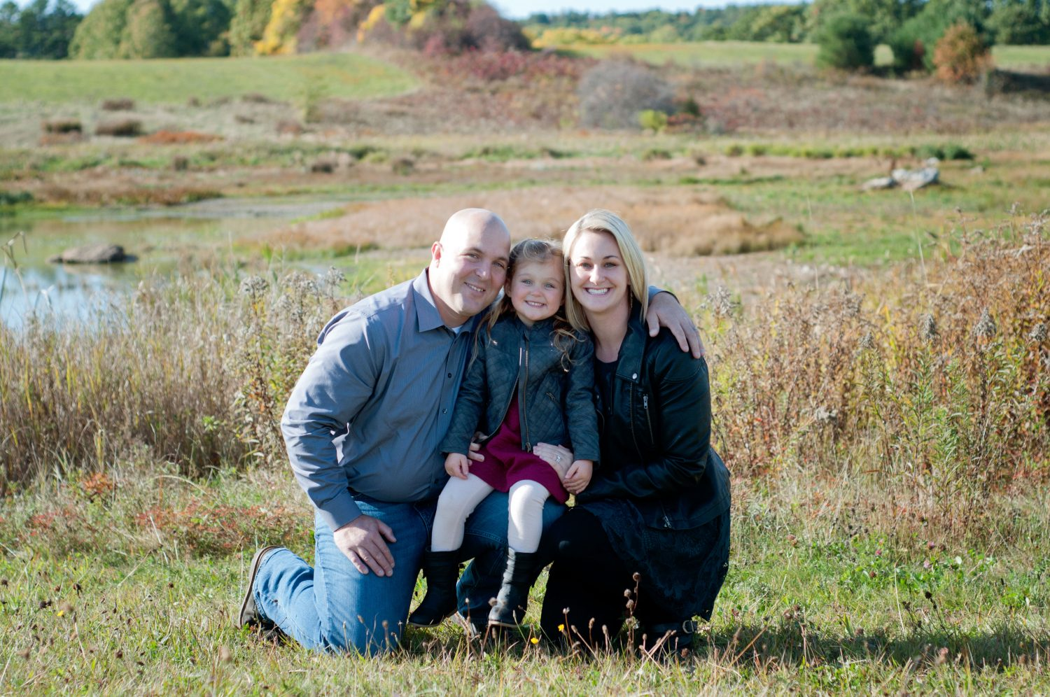 portrait of young family of 3 in an autum field
