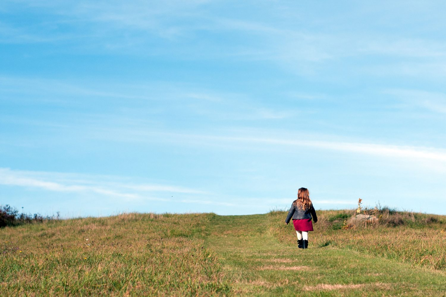 little girl walking up big grassy hill
