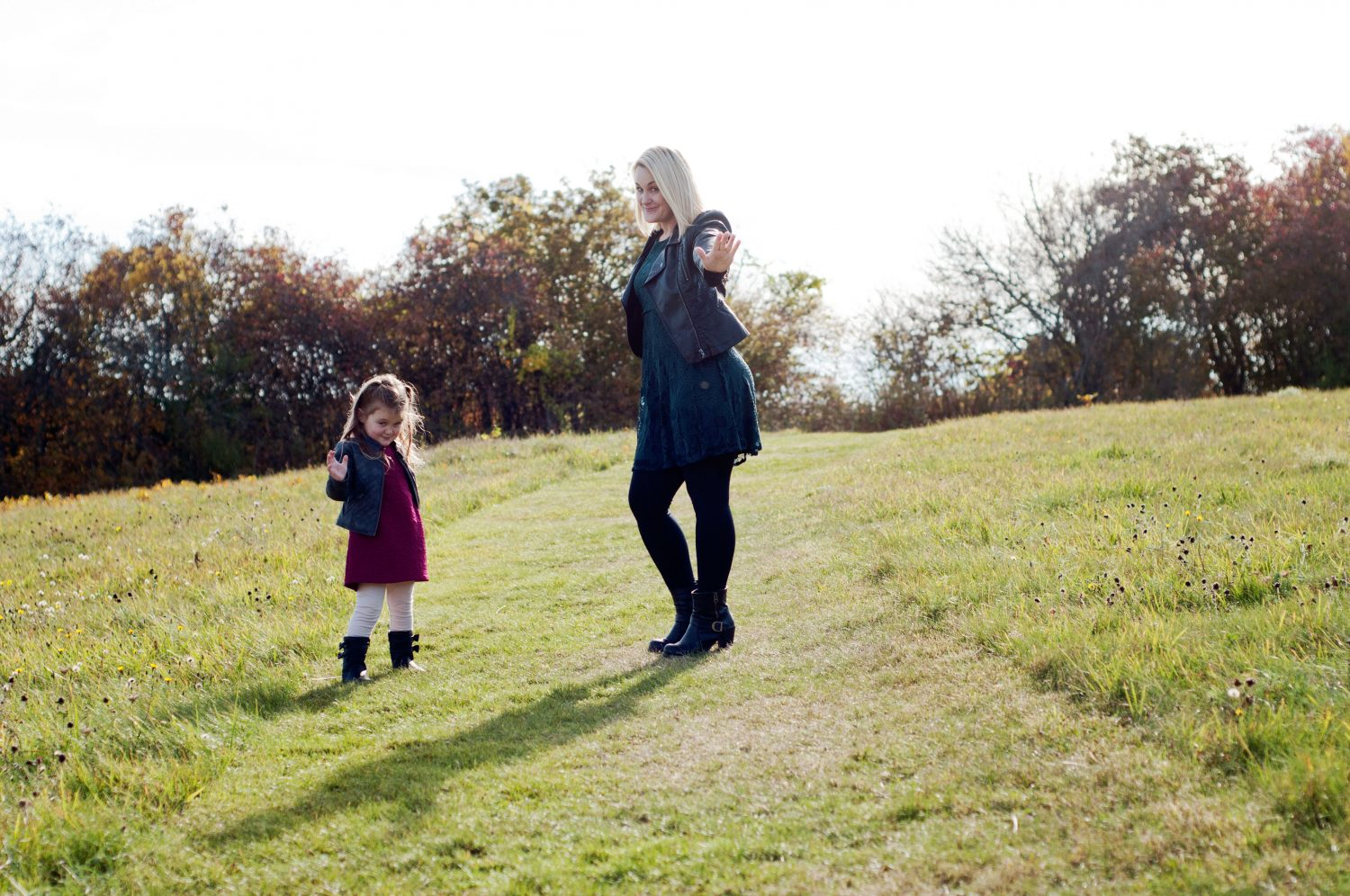 mother and daughter posing silly in a sunny field