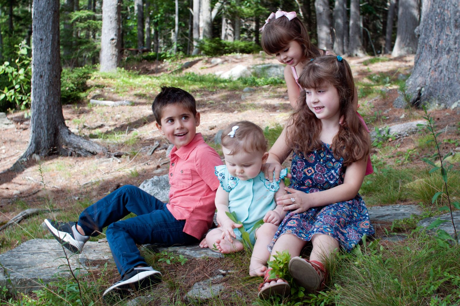candid portrait of four young children sitting together in the forest