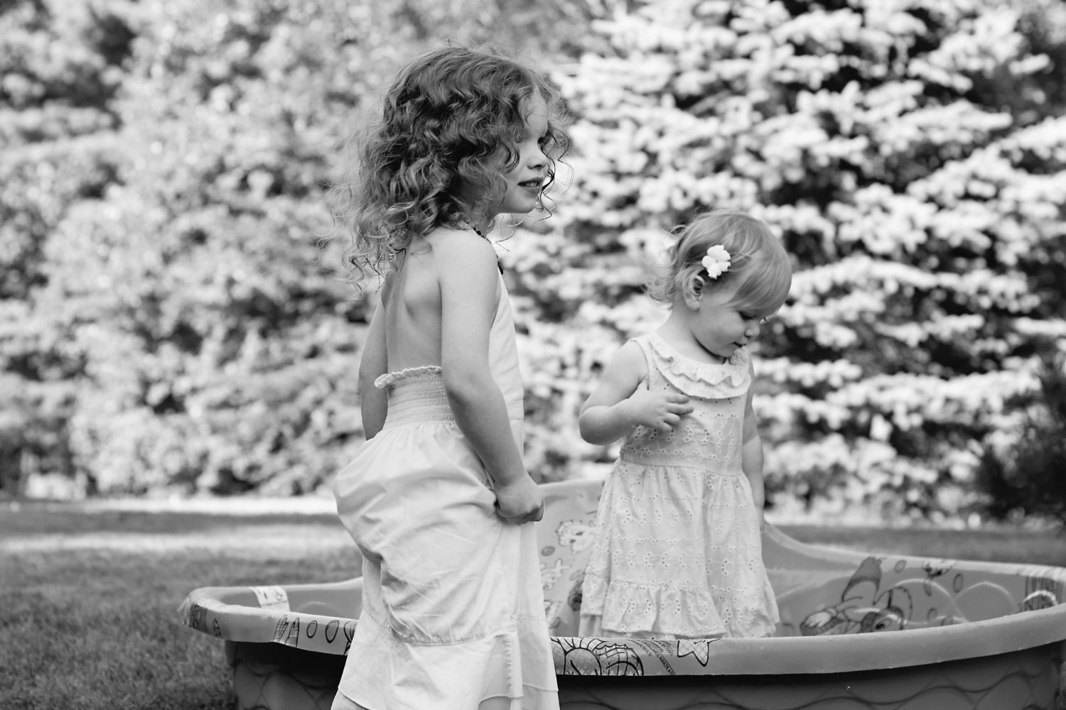 black and white photo of two young girls playing in a wading pool