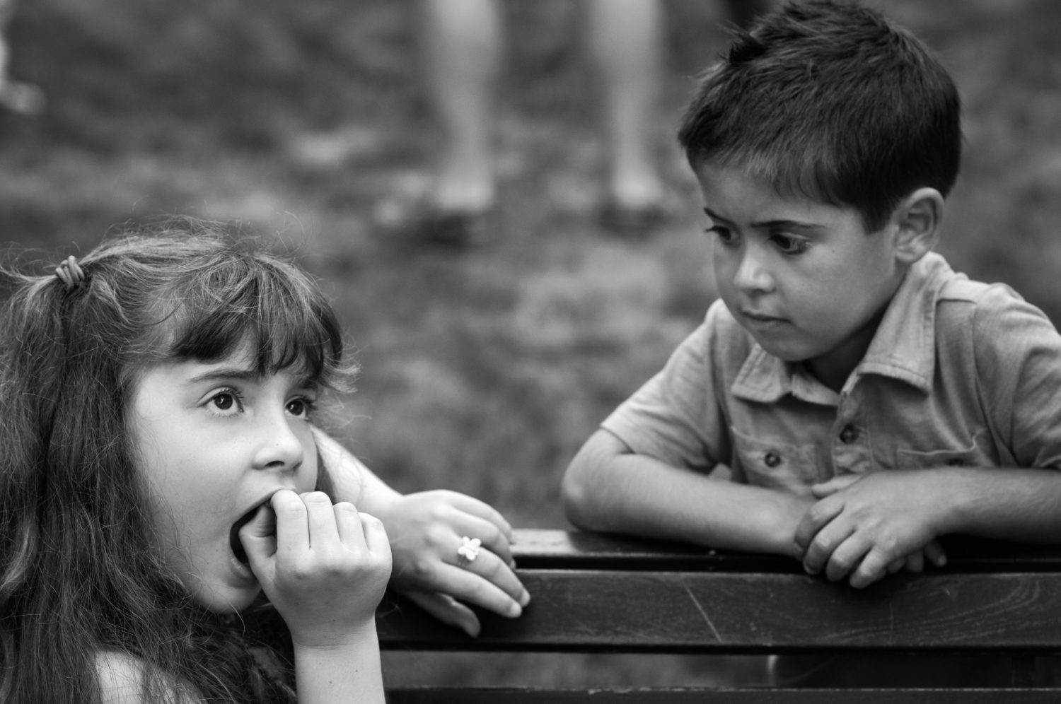 black and white photo of young girl wiggling her loose tooth while young boy watches