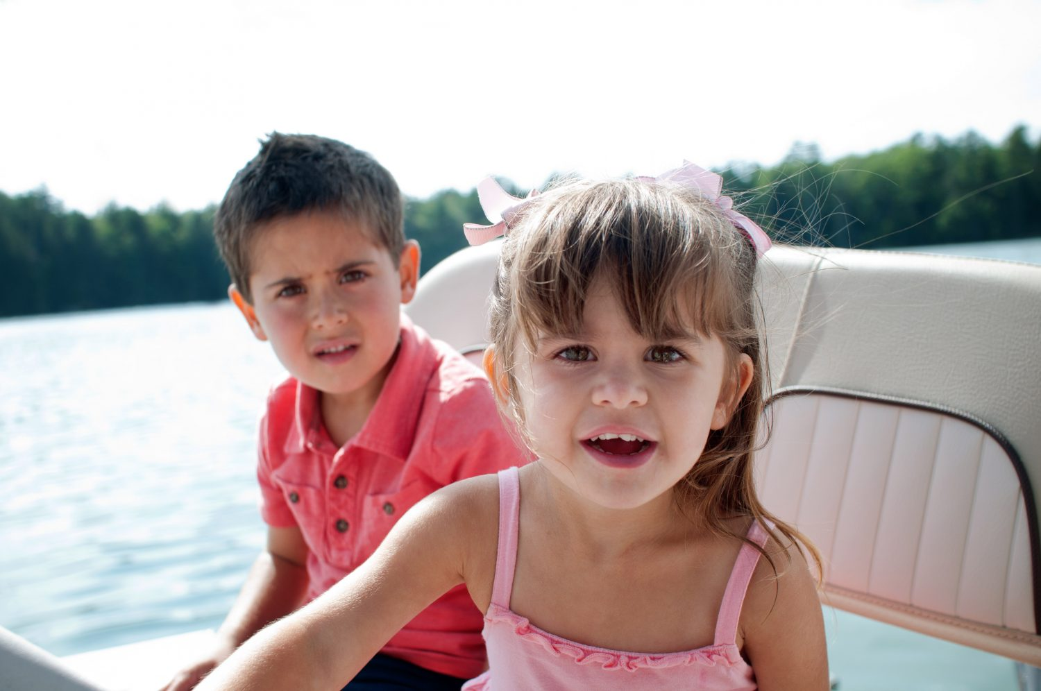 photo of little girl and boy sitting on boat