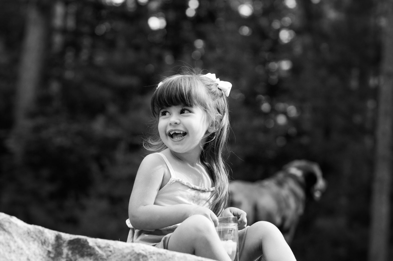 black and white photograph of young girl sitting on the ground laughing