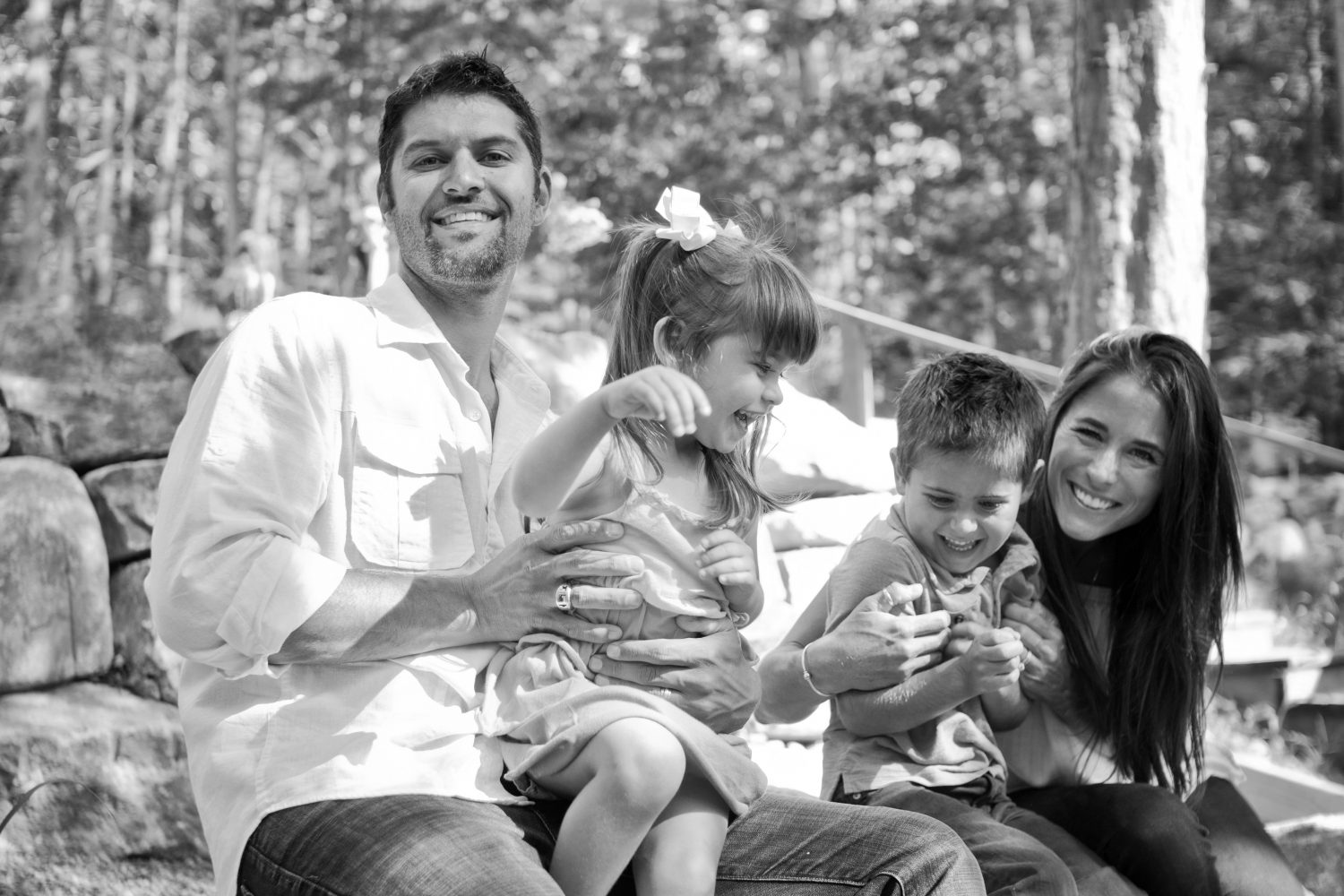 silly candid black and white photo of young family of four