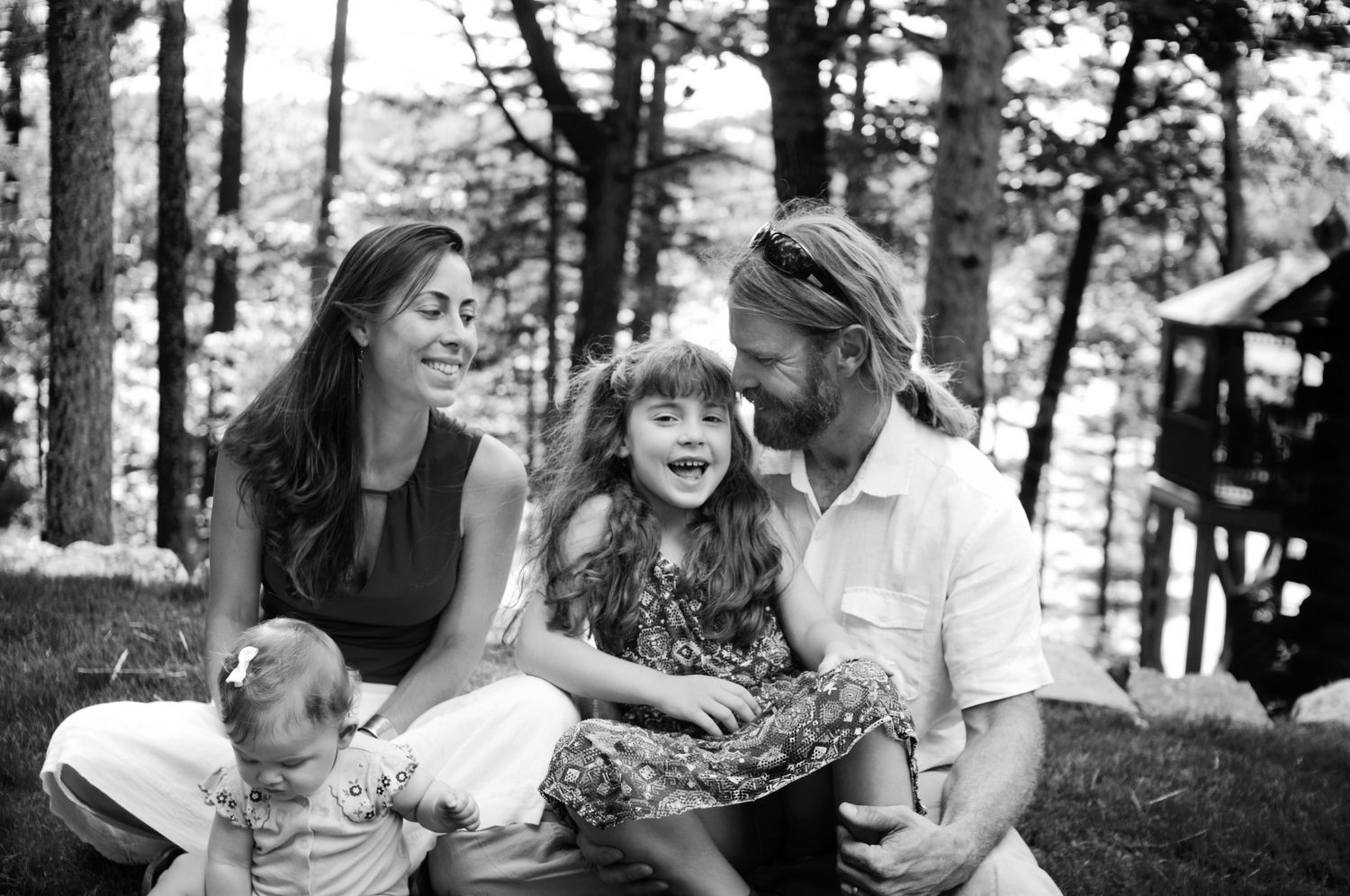 candid portrait of family of four sitting together in the grass