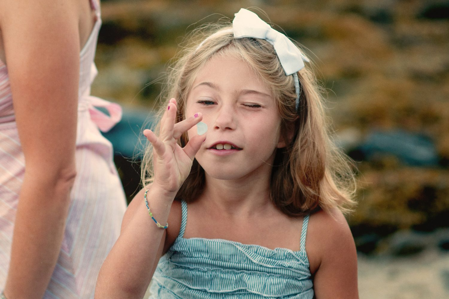 young girl looking at small blue pebble with one eye closed