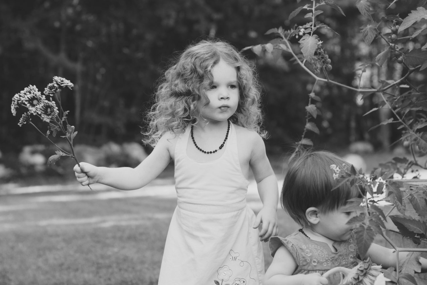 black and white photo of young girl gazing into the distance holding a bouquet of flowers