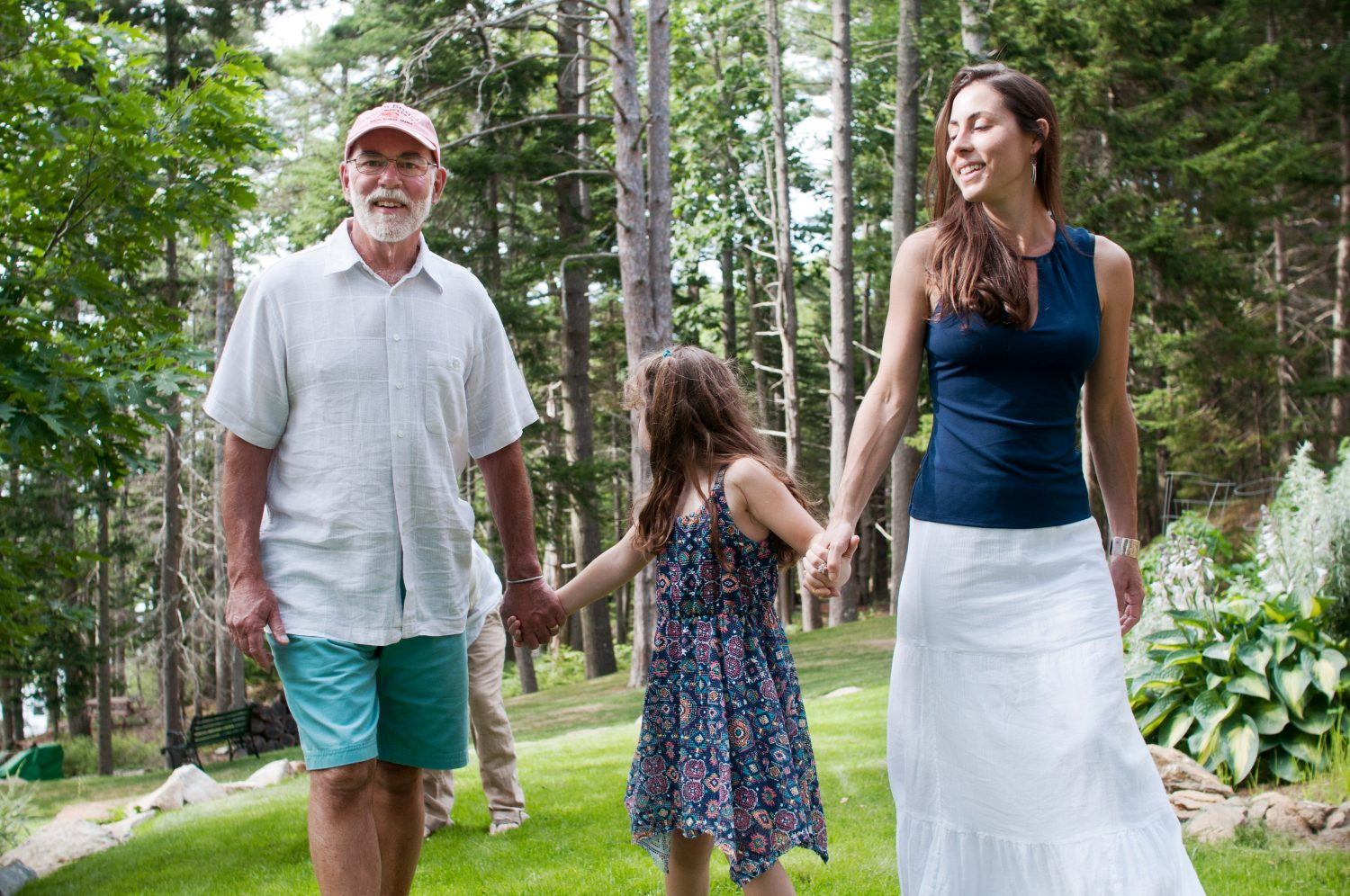 grandfather, daughter and granddaughter walking together through the grass holding hands