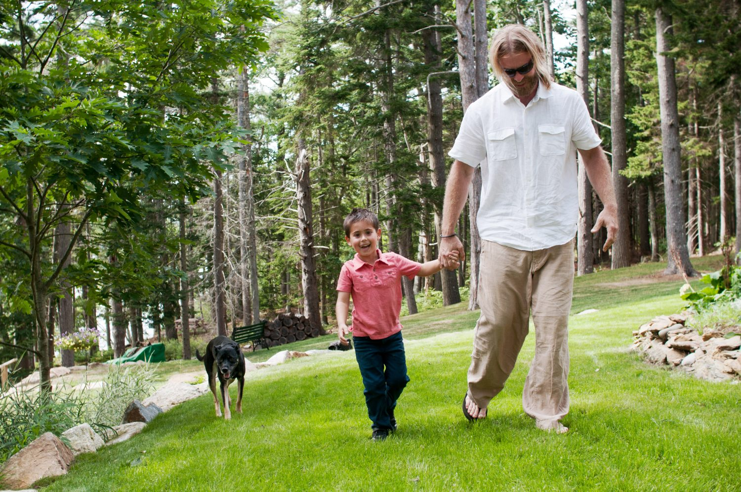 father and young boy holding hands and walking in the grass with older dog