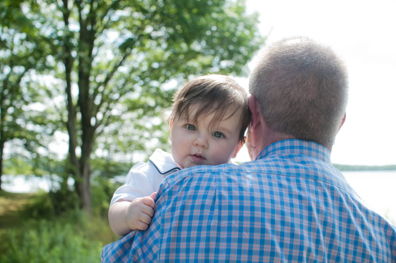 photo of baby boy looking at camera over the shoulder of his father