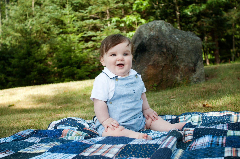 portrait of baby boy in blue sitting on quilt in grass