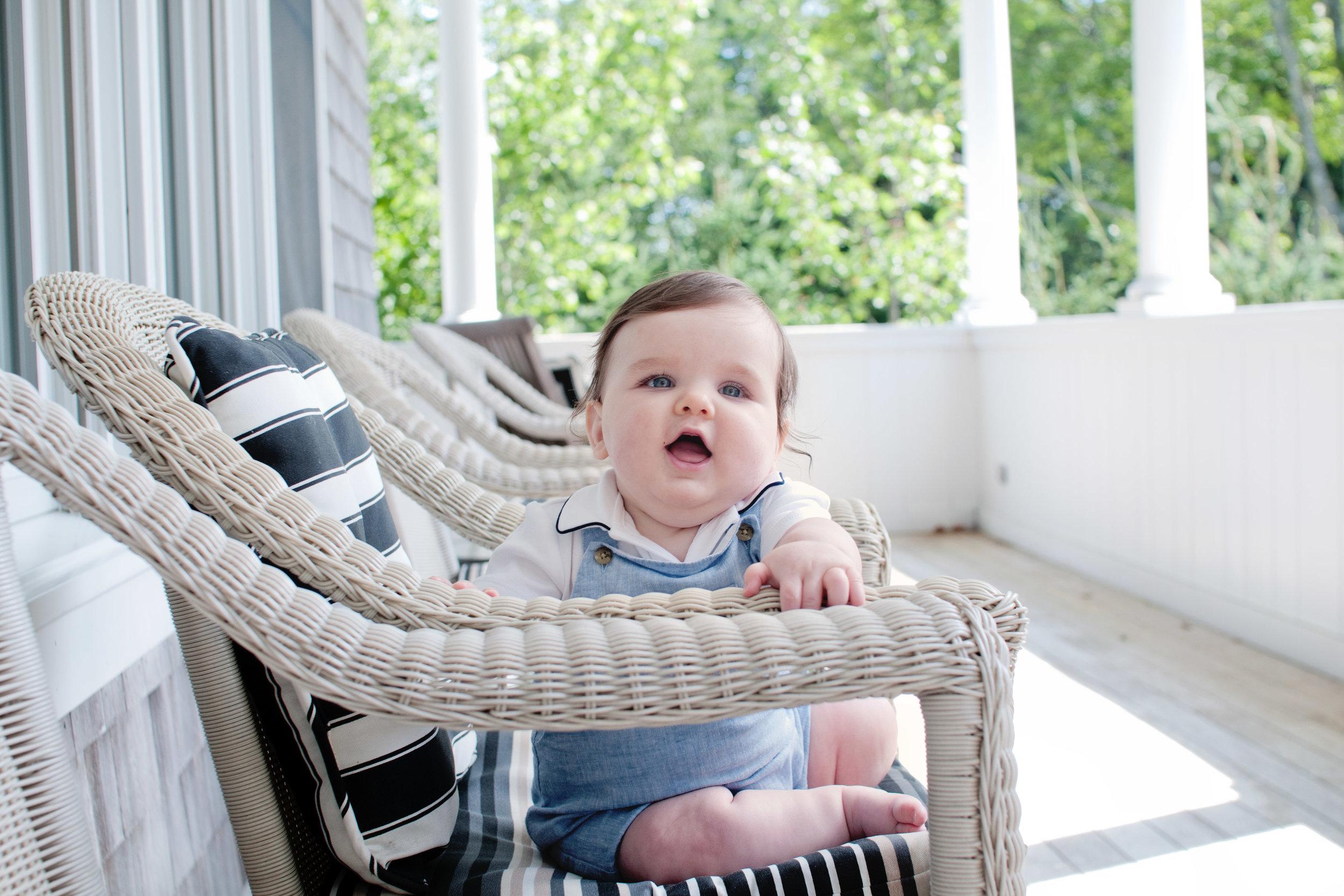baby boy sitting in wicker chair smiling