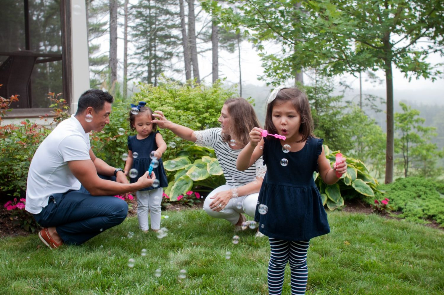 little girl blowing bubbles with her family
