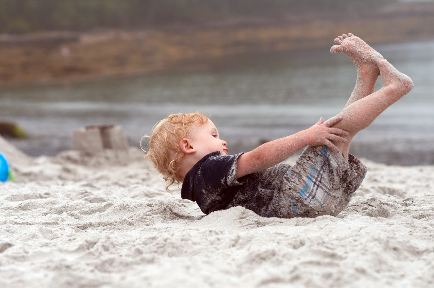 toddler rolling in the sand at Pemaquid Beach