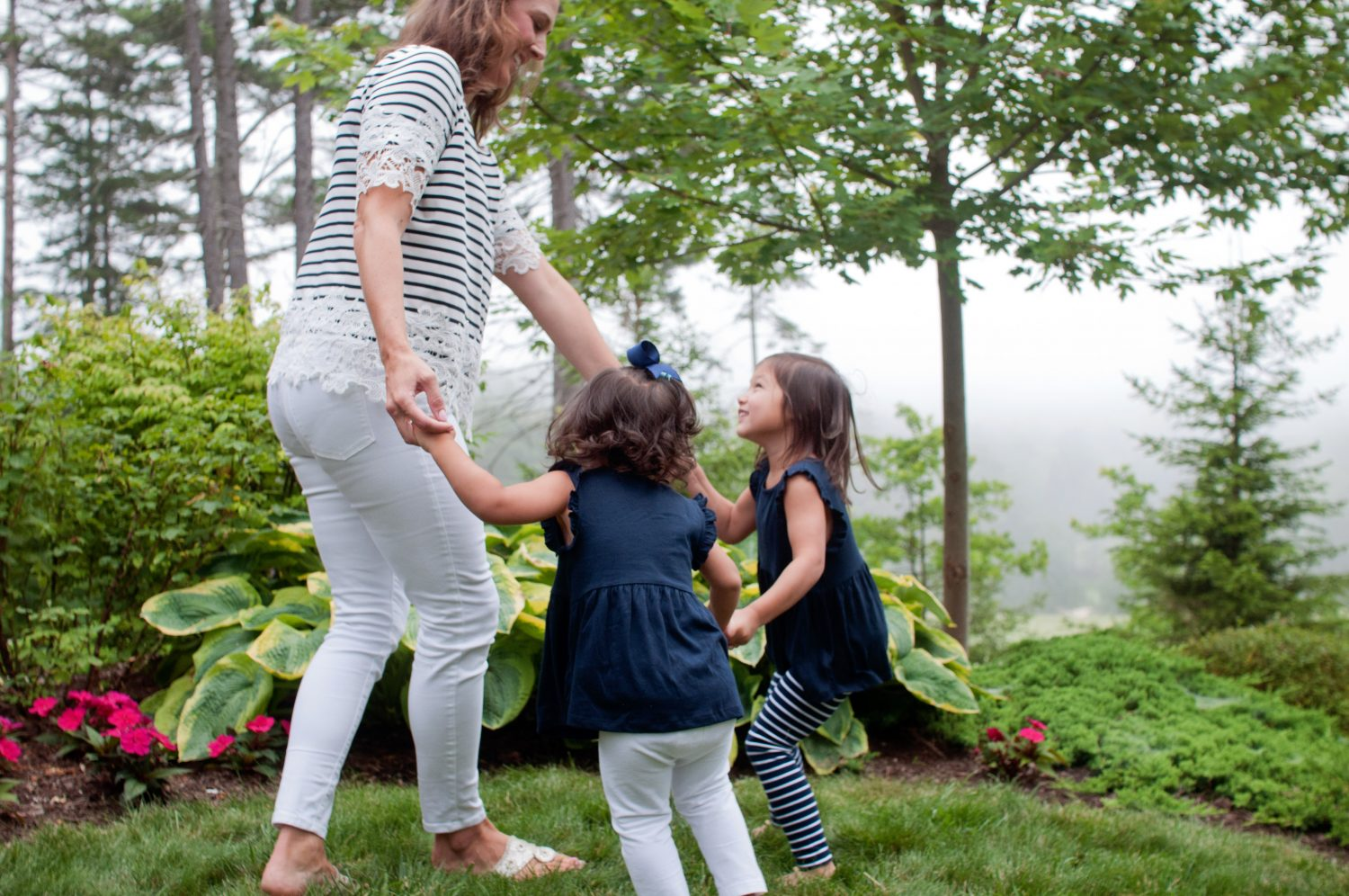 mother playing ring-around-the-rosey with two young daughters
