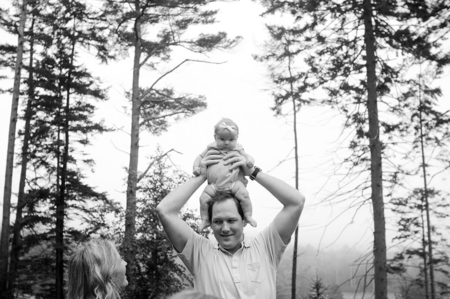 black and white photo of father holding baby daughter on his head while mother watches