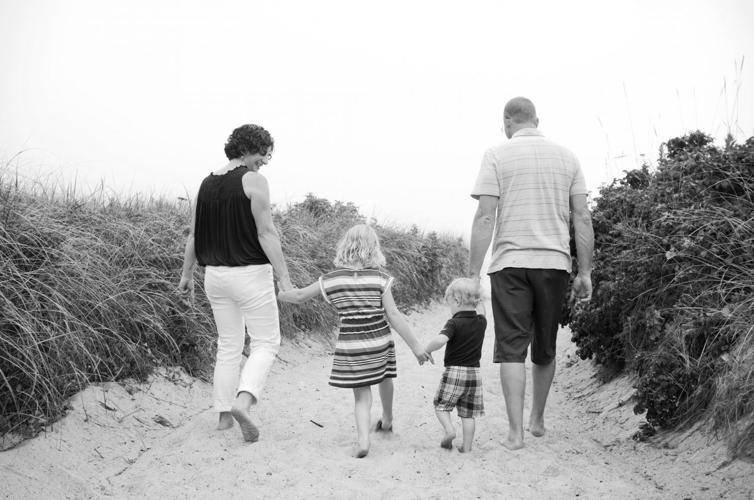 black and white photo of family of four holding hands walking on a beach path