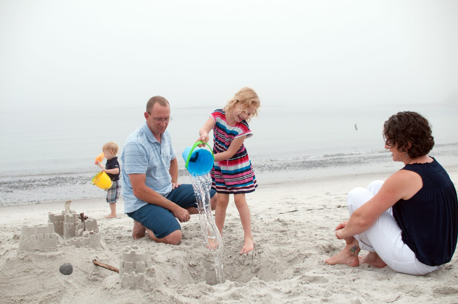 Little_girl_pouring_water_into_hole_in_sand