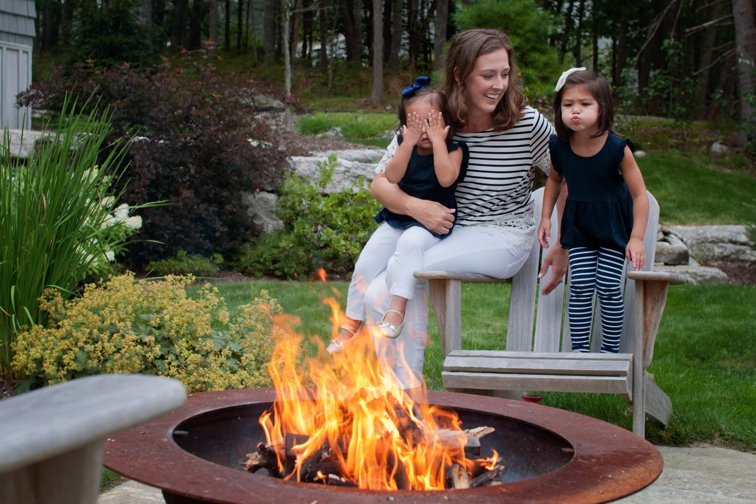 mother with two young daughters sitting by camp fire
