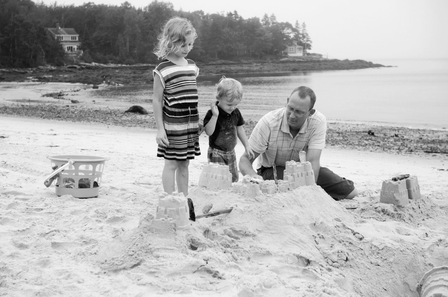 Black_and_white_image_of_family_building_sandcastle