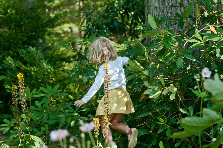 little girl running through the bushes