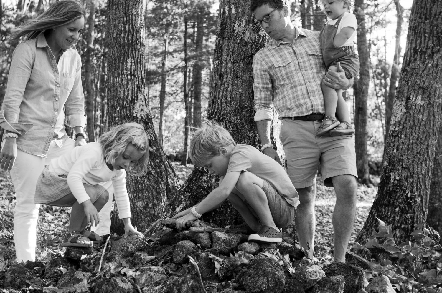 family of five building small forts in the woods