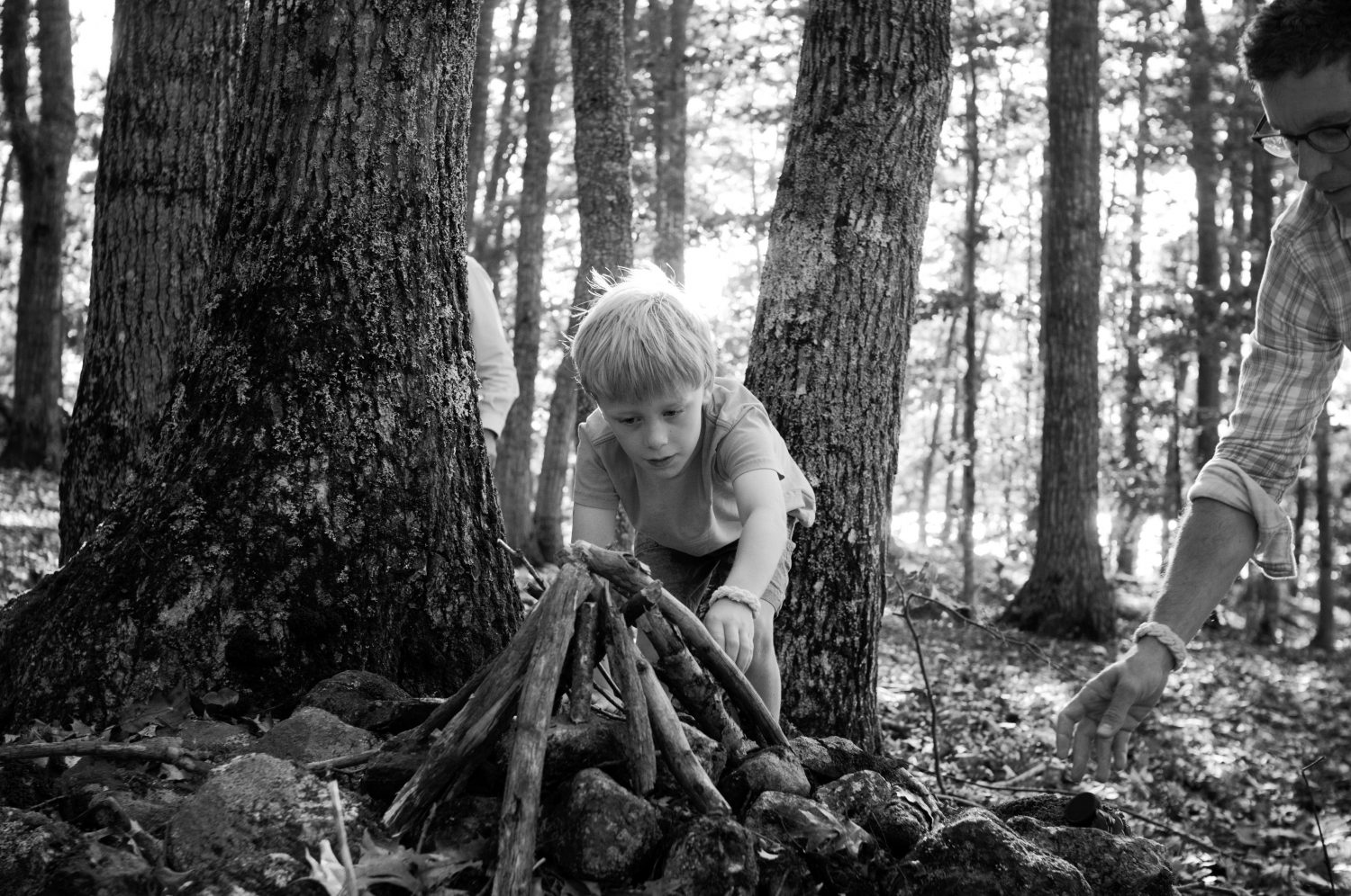 young boy building small wooden tee pee in the forest