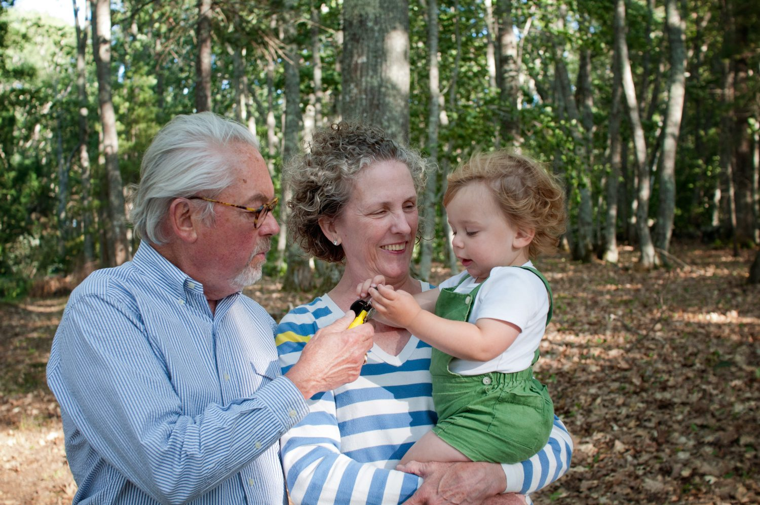 candid photo of grandparents holding toddler boy in the forest