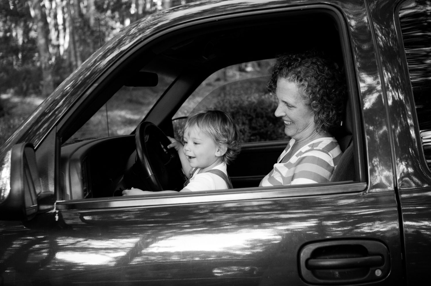 toddler sitting on grandmothers lap in the front seat of truck