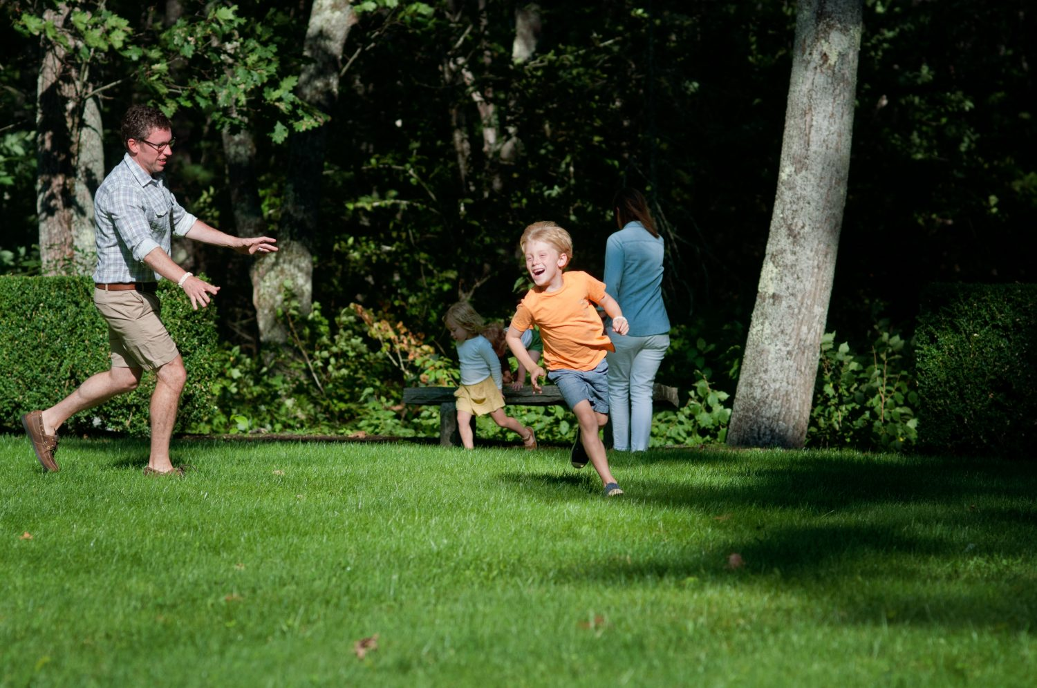 young family playing chase in the lawn