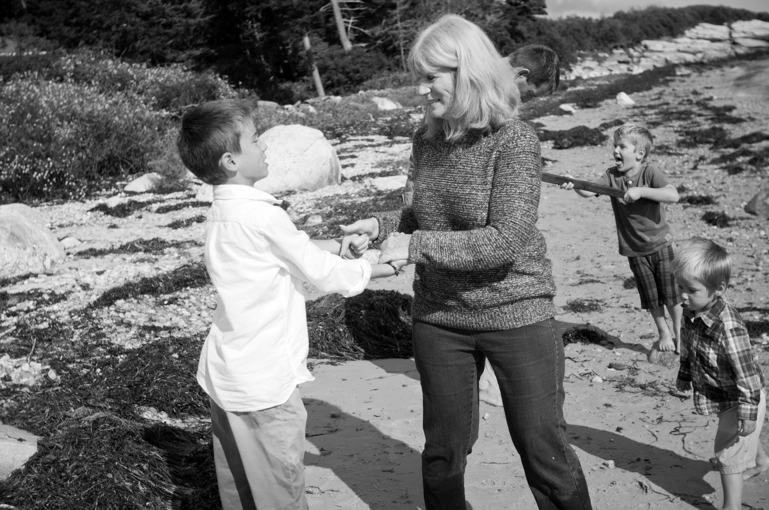 three young boys playing with their grandmother on the beach