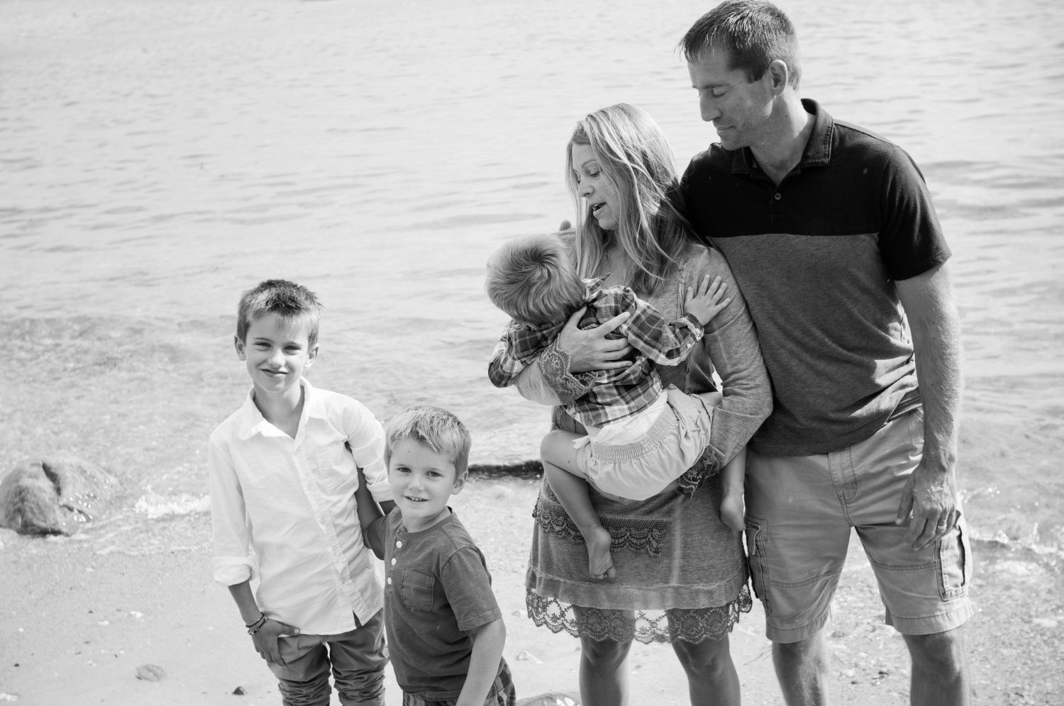 candid black and white photo of family of five at the shore