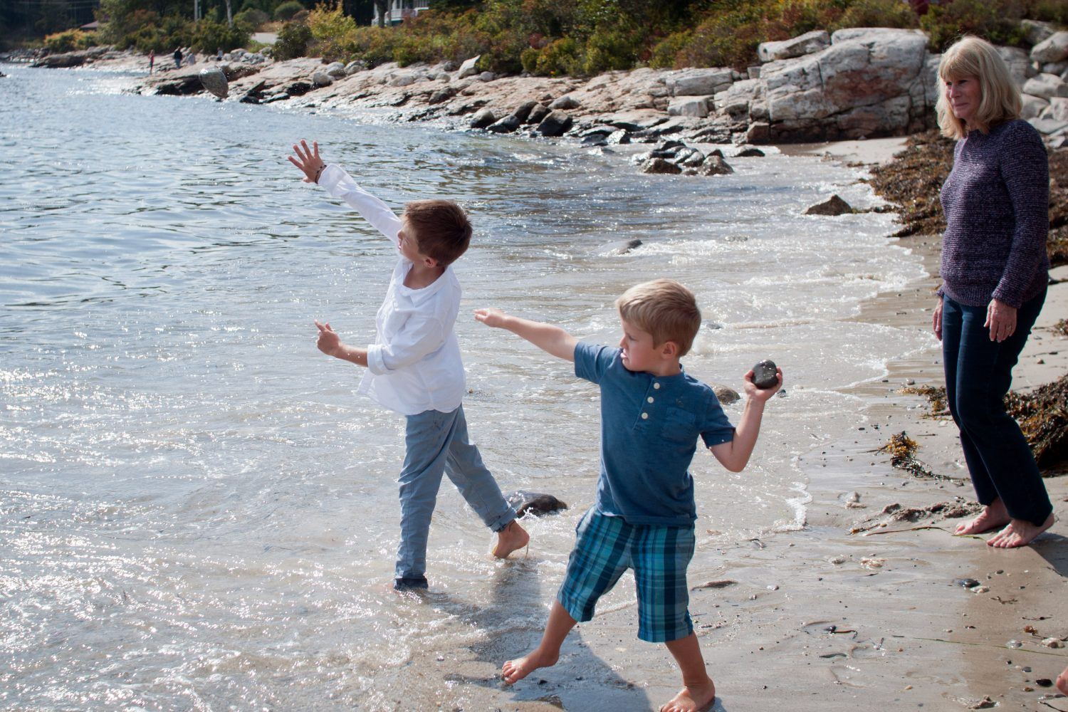 two young brothers throwing rocks into the water while grandmother watches