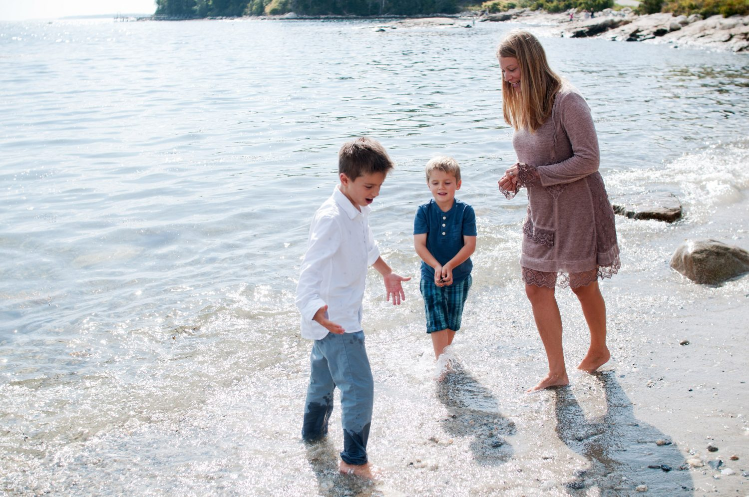 mother playing with her two sons in the ocean
