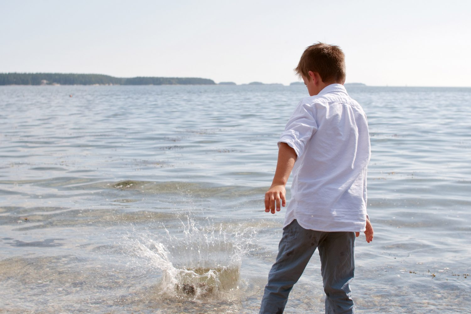 young boy throwing big rock into the salt water