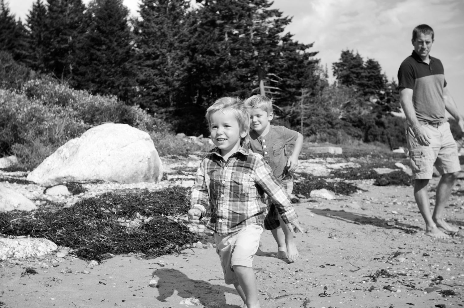 black and white photo of two young boys running along the shoreline while father watches