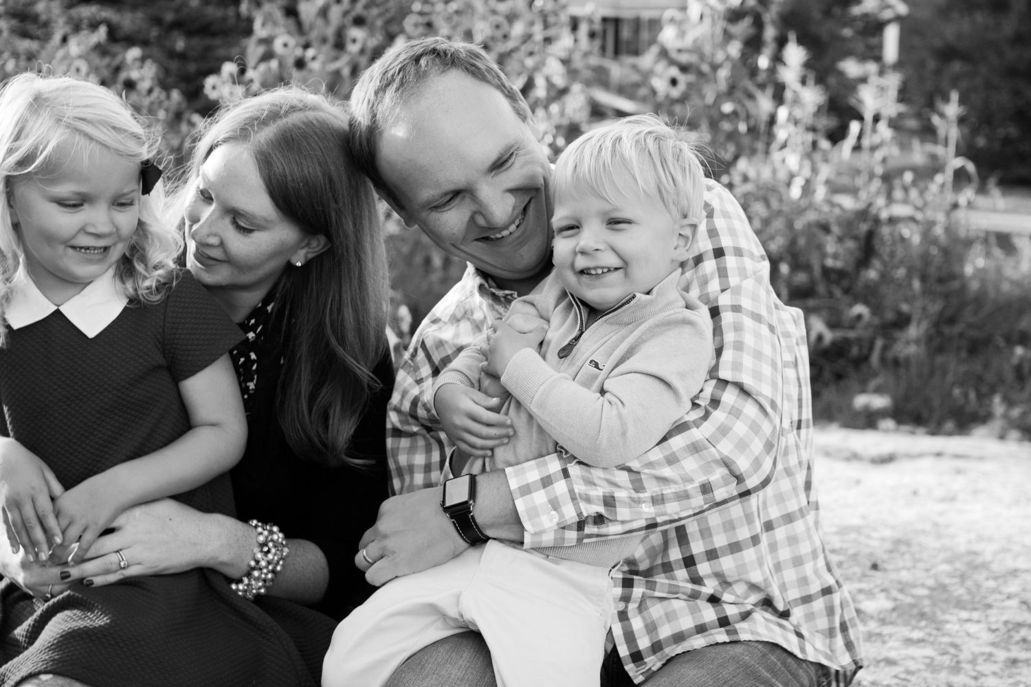 candid black and white photo of young family of four