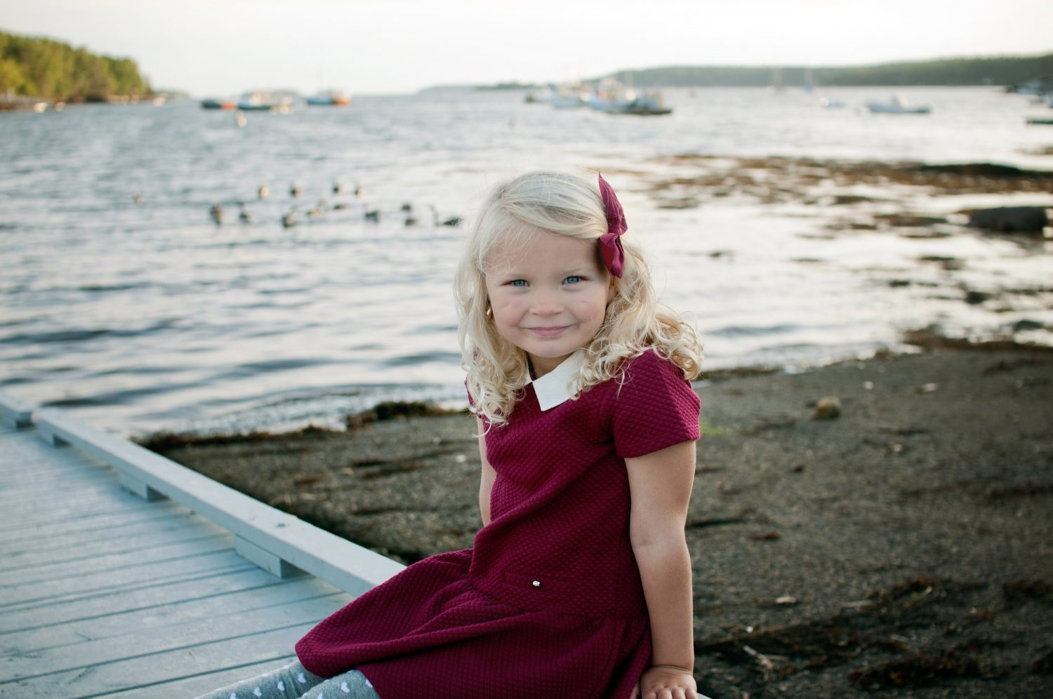 portrait of young girl in maroon dress and hair bow sitting by the waters edge